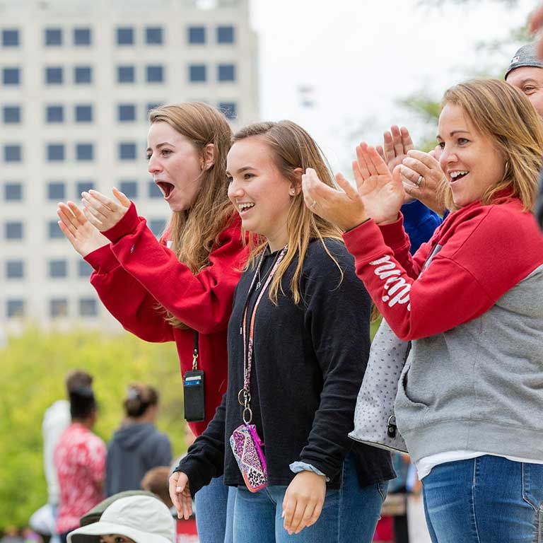 Students cheer on their friends on the side of the canal.