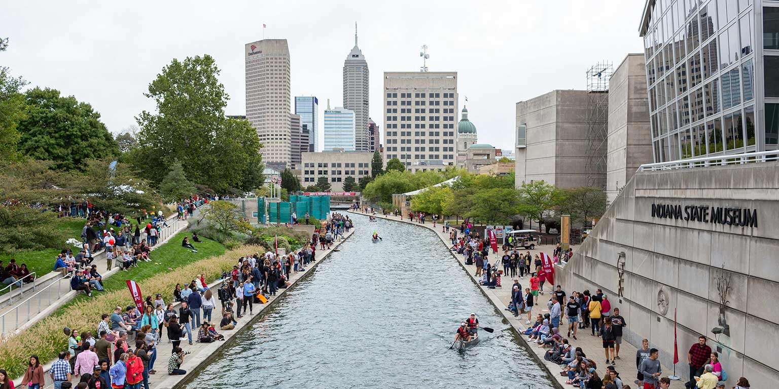 An aerial view of the race on the canal with the Indianapolis skyline in the background.