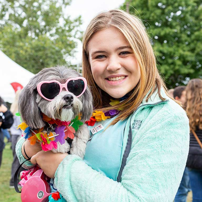 A girl poses with her dog that's dressed up in sunglasses and a lei for the Regatta dog costume contest.