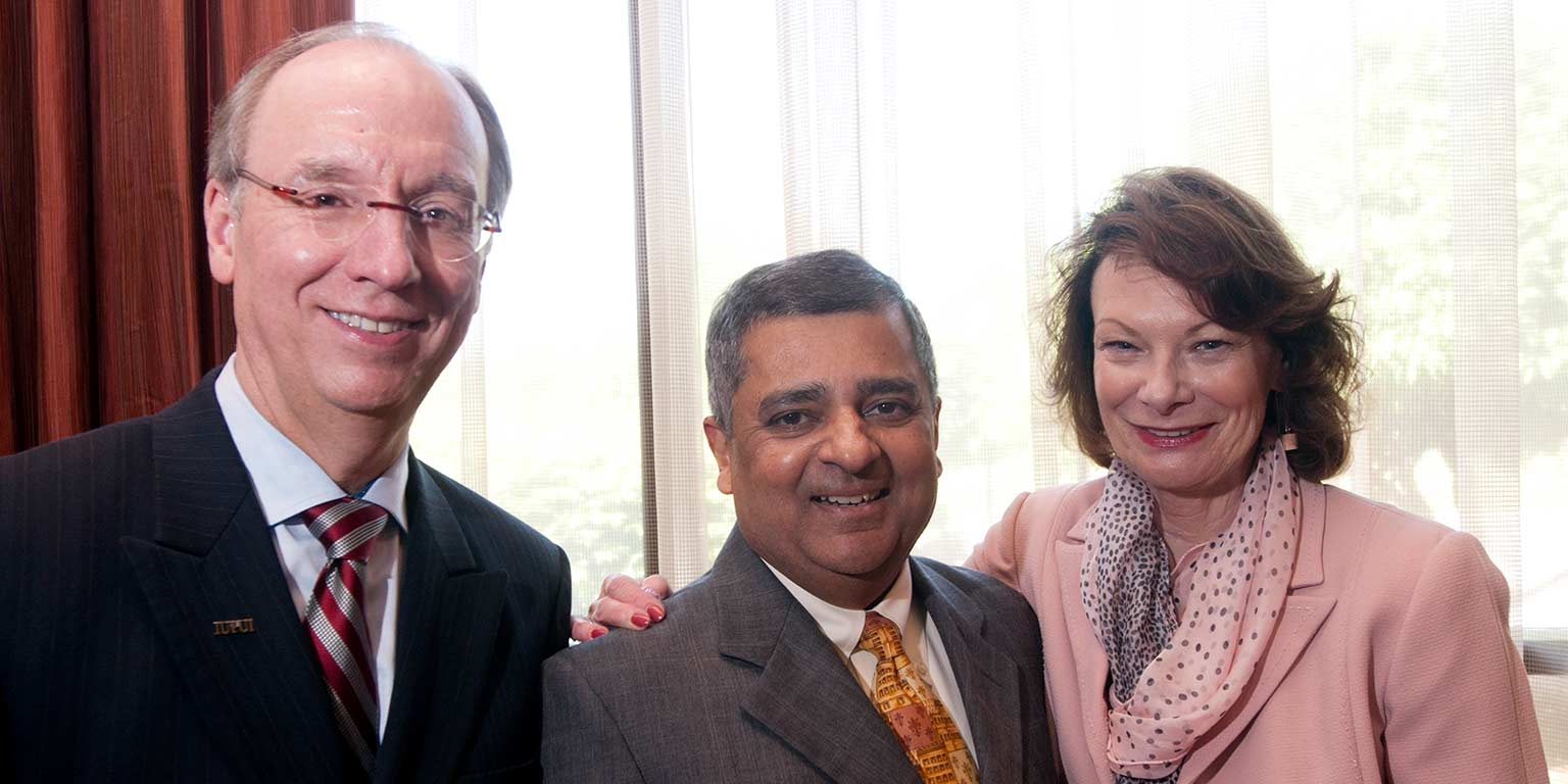 Former IUPUI Chancellor Charles Bantz stands with his wife Sandra Petronio and former Executive Vice Chancellor Uday Sukhatme.