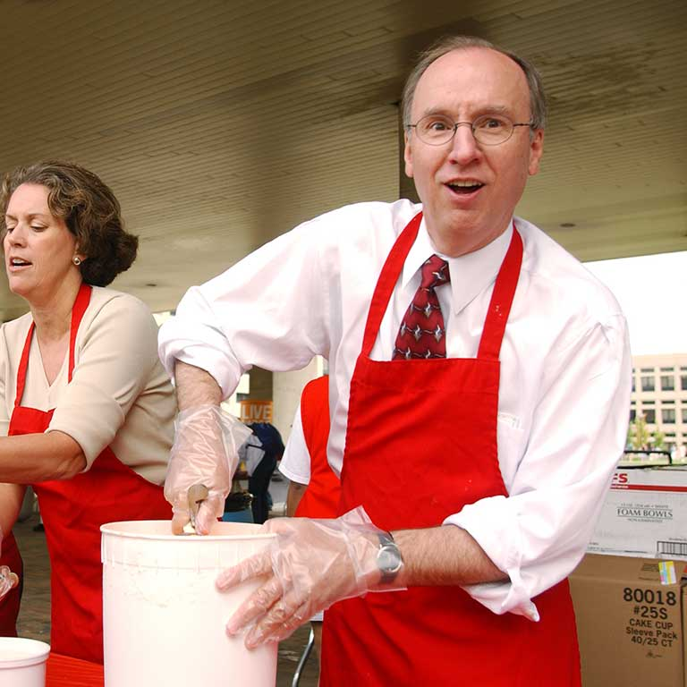 Former IUPUI Chancellor Charles Bantz scoops ice cream at his first Weeks of Welcome Ice Cream Social.