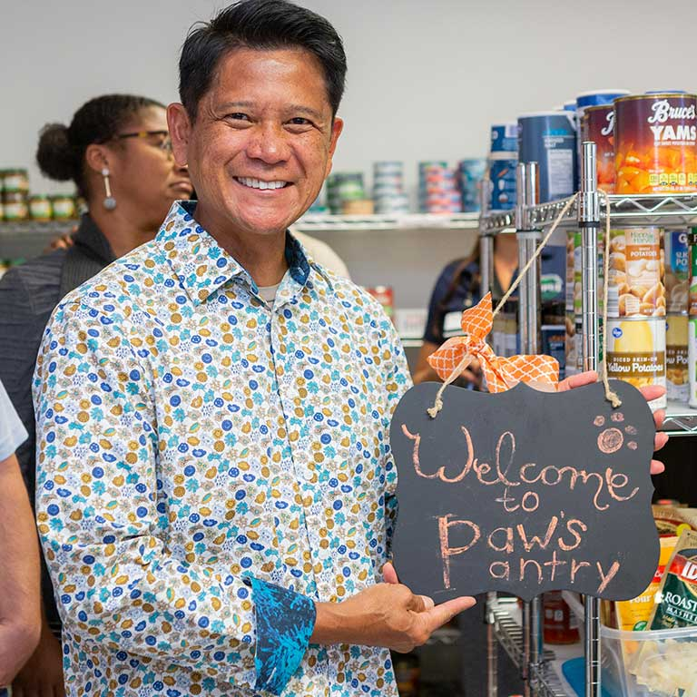 Merlin Gonzales with the 'Welcome to Paw's Pantry' sign.