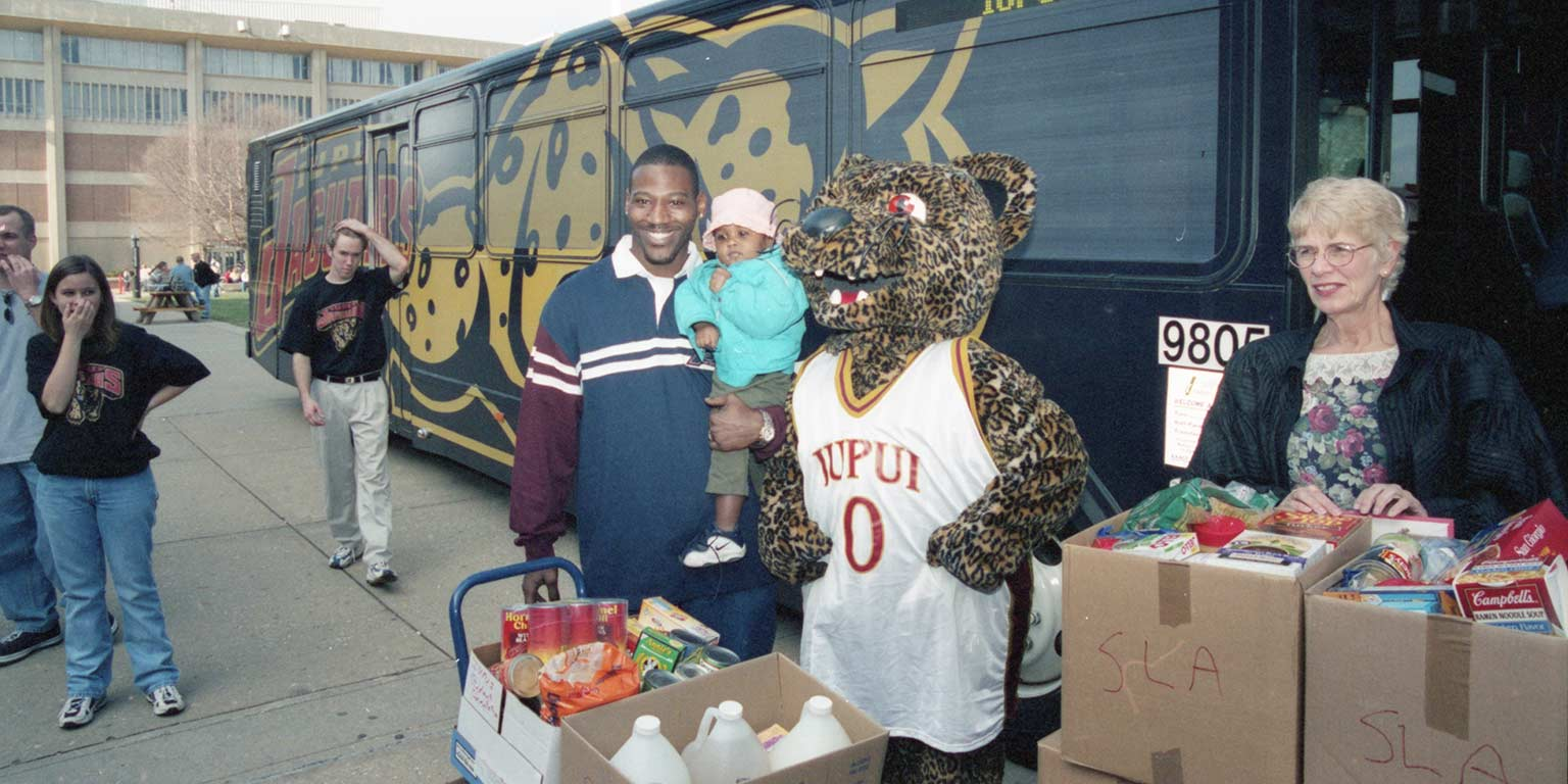 Jake Manaloor as Jinx the mascot during a Jam the Jaguar Bus food donation event in 1999.