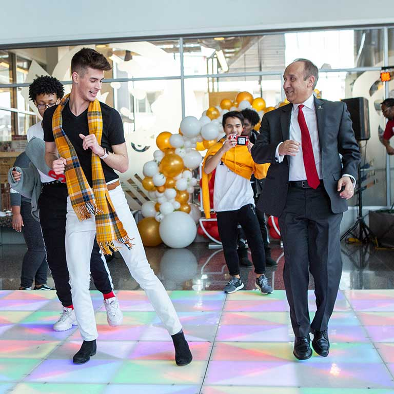Chancellor Nasser Paydar dances with students at IUPUI's 50th Anniversary Birthday Bash in 2019.