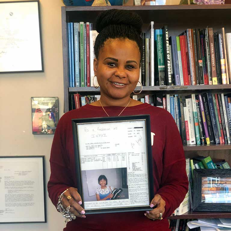 Khalilah Shabazz stands with a picture of herself when she was a freshman at IUPUI.