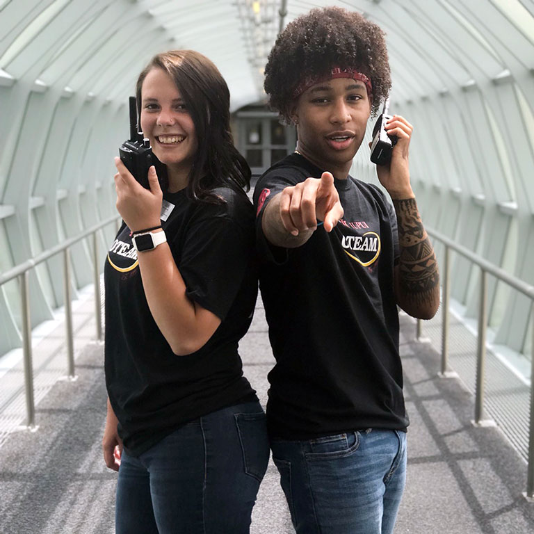 Will Smith poses with an OTEAM colleague and their walkie talkies in one of IUPUI's famous gerbil tubes.