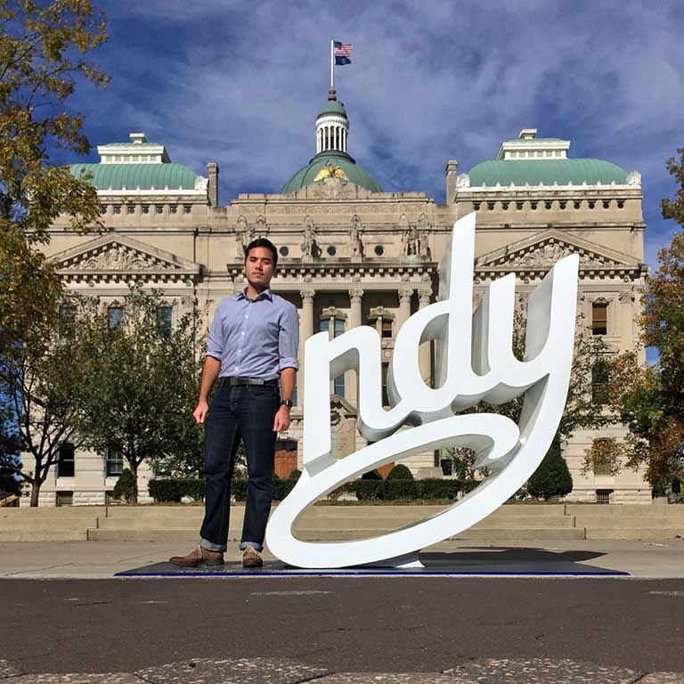 Andre Zhang Sonera stands as the 'I' of 'Indy' in front of the Indiana Statehouse.