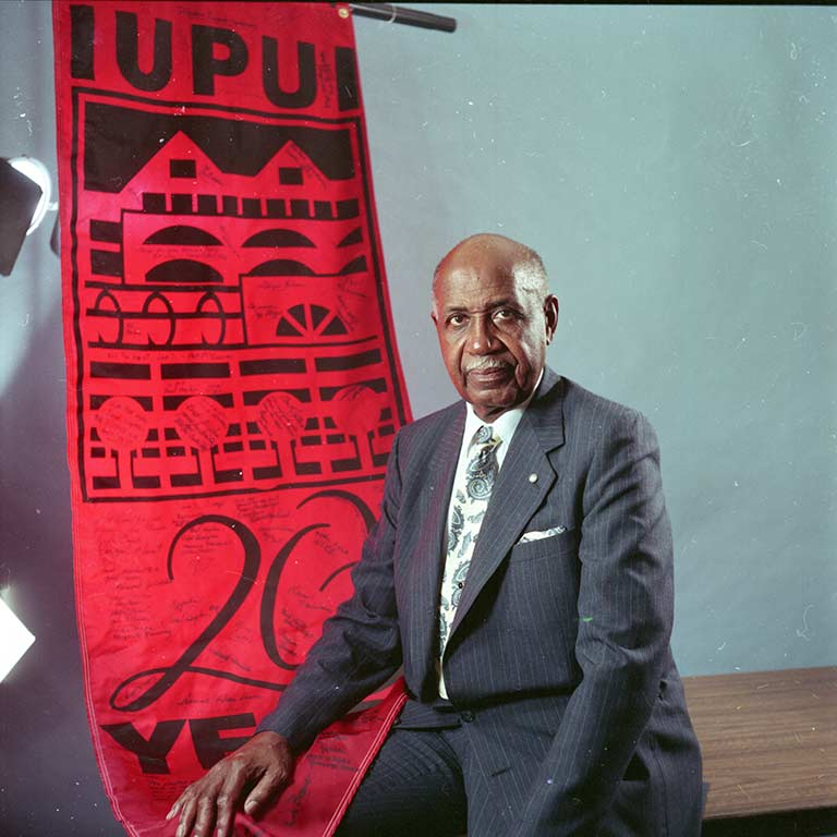 Joseph Taylor sits with a 20 years of IUPUI banner.