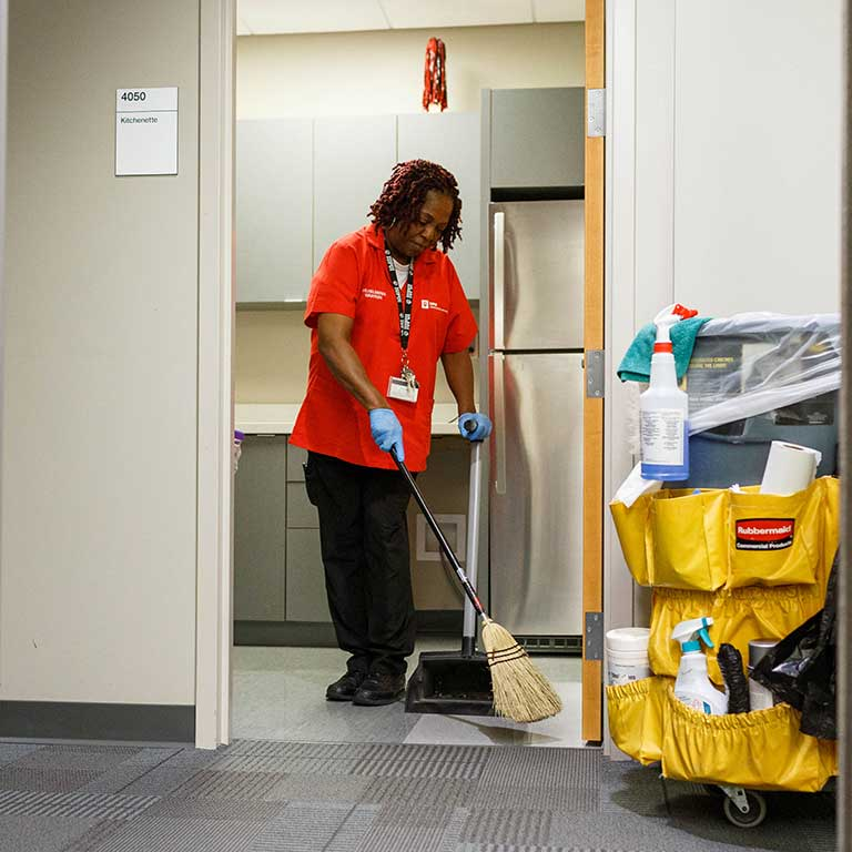 Wilhelmenia sweeps up the kitchen area on the fourth floor of University Hall.