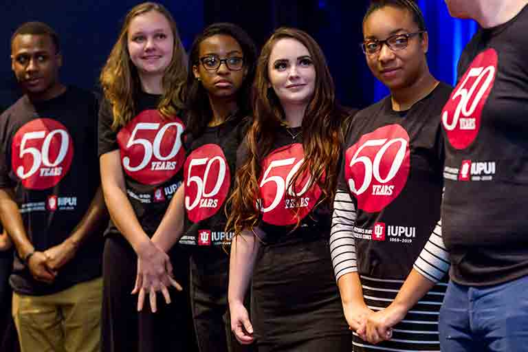 Six IUPUI student volunteers wearing 50th Anniversary T-shirts stand on stage during an event.
