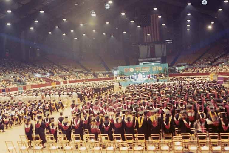 A stadium packed with IUPUI's first graduates in caps and gowns. Color photo.