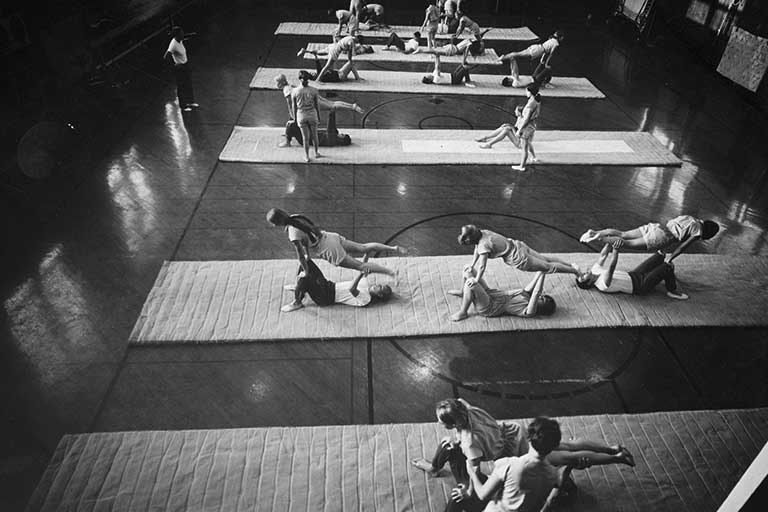 Rows of students sitting on mats practice gymnastics. Black and white photo.