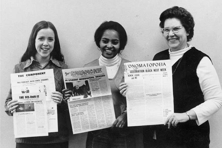 Two students and an advisor hold previous campus newspapers, The Component and Onomatopoeia, as well as the new Sagamore student publication. Black and white photo.