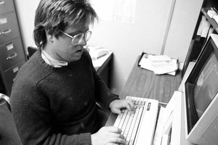 A reporter for the Sagamore types at a computer. Black and white photo.