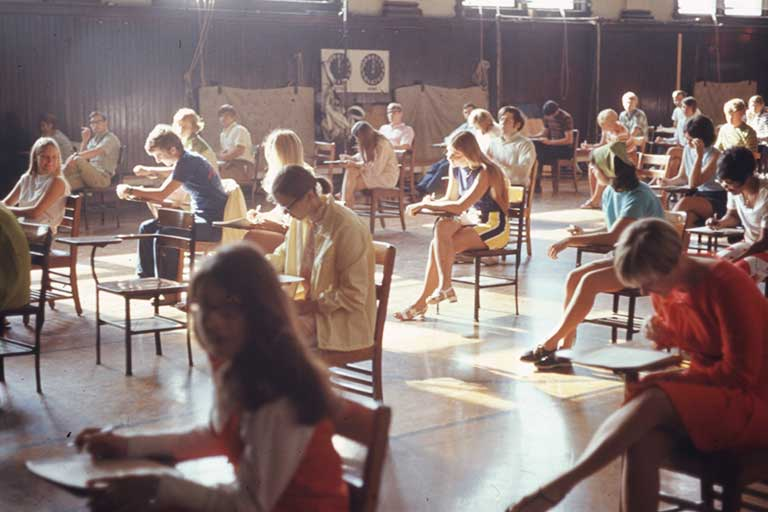 Students sitting at wooden desks take a test in the German House gymnasium, home of the Normal College. Color photo.